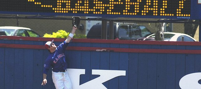 KU senior outfielder Ryne Price leaps for, but can't quite reach, a home run by Missouri. The teams split a doubleheader Sunday at Hoglund Ballpark. KU won the opener, 7-6, but lost the nightcap, 12-1.