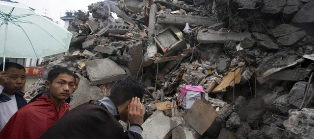 Residents listen for sounds of life in the rubble of a collapsed building in Dujiangyan, in southwestern China's Sichuan Province. Thousands of people are believed buried in the debris of collapsed buildings.