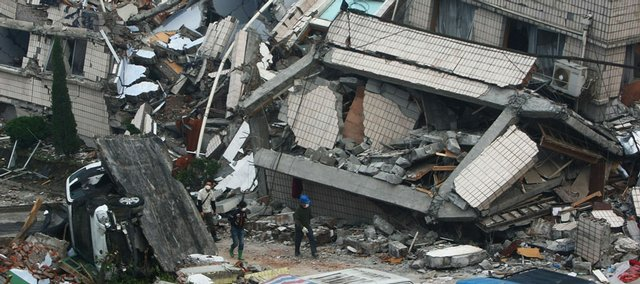 Rescuers search for victims in the debris of collapsed buildings Friday in China's Yingxiu Township. China struggled to bury its dead and help tens of thousands of injured and homeless Friday when a powerful aftershock brought new havoc four days after an earthquake.