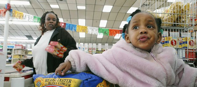 Lynda Wheeler shops with her daughter, Jaime, 2, shortly after midnight on May 1 at One Stop Food & Liquors on Chicago's South Side. The market doors open at midnight on the first of each month so Wheeler and a dozen or so others can start shopping the instant they have access to the new month's allotment of food stamps.