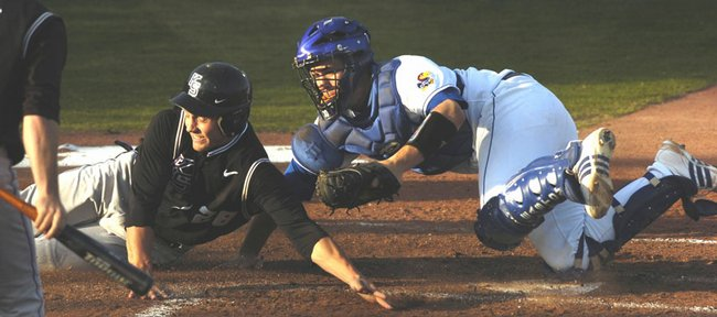 Kansas State's Jason King, left, gets tagged out by Kansas University catcher Buck Afenir on a play at the plate. The Wildcats opened a crucial Big 12 series with a 5-0 victory over the Jayhawks on Friday at Hoglund Ballpark.
