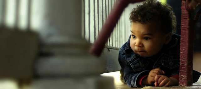 Eighteen-month-old Jesiah Haider-Markel crawls around the front porch of his Lawrence home May 9 under the watch of his parents Don and Michele Haider-Markel. The Haider-Markels received Jesiah as foster parents when he was 6 months old, and after several months eventually were allowed to adopt him when the child's biological parents had terminated their rights.