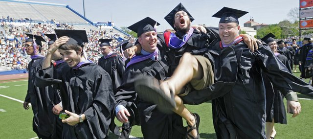 Kansas University graduate Marshall Hilton, of St. Louis, swings into the air while holding onto his classmates during commencement on Sunday at Memorial Stadium. About 4,000 graduates took the traditional walk down Campanile hill to mark the completion of their degrees.