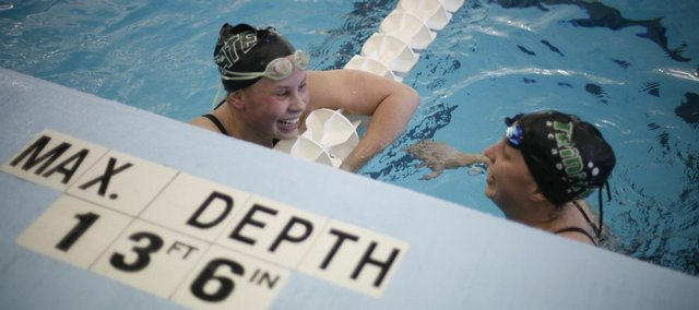 Free State High's Morgan Flannigan, left, talks with Rebecca Swank of Wichita Trinity. Flannigan finished second to Swank in the 500 freestyle at the state championships Saturday in Topeka. As a team, the Firebirds finished second to Blue Valley Northwest.