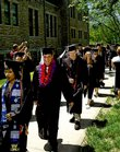 Baker University graduates pass by faculty members Sunday as they marched to Collins Gym for commencement.