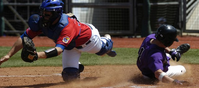 KU catcher Buck Afenir, left, is unable to pull in a throw to home in time to tag out a K-State runner.