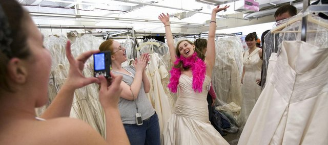 "Rebecca Stamilio, left, photographs her friend Erin Robertson as they shop for wedding dresses during the ""Running of the Brides"" at Filene's Basement in New York in this Feb. 29 file photo. For the typical American couple, putting on a wedding these days means cutting some corners. Many brides are buying gowns at discount retailers and couples are looking for cheaper places to honeymoon."