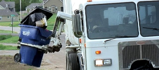 Randy Weldon, of Weldon Enterprises, picks up trash in Eudora with an automated trash truck. Students at Kansas University say such trucks could ease curbside recycling, but a Lawrence official says they're not the best choice for the city.
