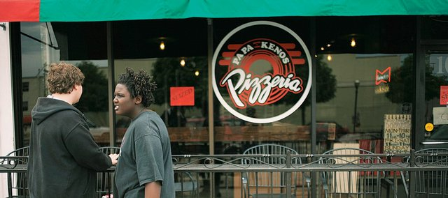 "Passers-by  read the ""Seized"" sign displayed Wednesday in the window of Papa Keno's, 1035 Mass. The sign read, ""This property has been seized for nonpayment of taxes, and is now in the possession of the state of Kansas."""