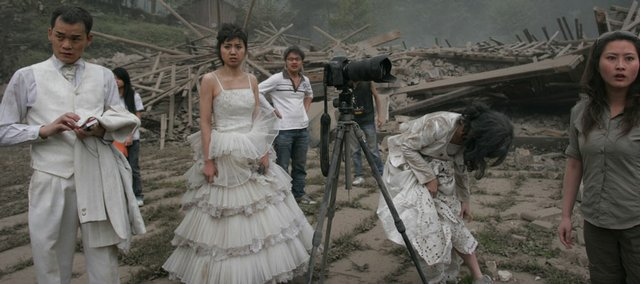 A couple reacts immediately after an earthquake struck during their wedding photo shoot May 12 at a deserted Catholic seminary in Pengzhou, China. Five couples were having wedding photos taken when the earthquake struck, and all escaped without injury.
