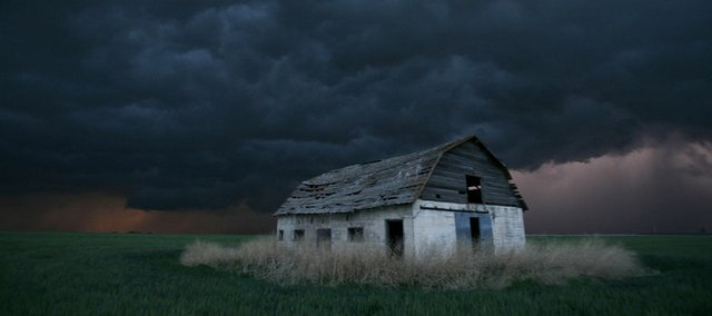 An old barn stands in a wheat field as a severe thunderstorm passes in the distance May 22, 2008, near Ogallah, Kan. Severe thunderstorms dropped tornadoes across much of northwest Kansas and northern Colorado.
