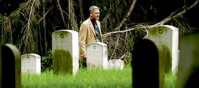 Kendall Gott walks through the The U.S. Military Prison Cemetery at Fort Leavenworth, which is the final resting place for 298 unclaimed bodies of soldiers who died in the United States Disciplinary Barracks.
