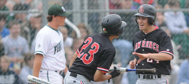 Lawrence High's Jake Green, right, is greeted at home plate by teammate Dorian Green after scoring the go-ahead run in the sixth inning against Free State Friday, May 23, 2008 at the Hummer Sports Complex in Topeka. Left is Free State pitcher Caleb Gress.