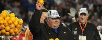 Kansas coach Mark Mangino holds aloft an orange as KU athletic director Lew Perkins, right, looks on.