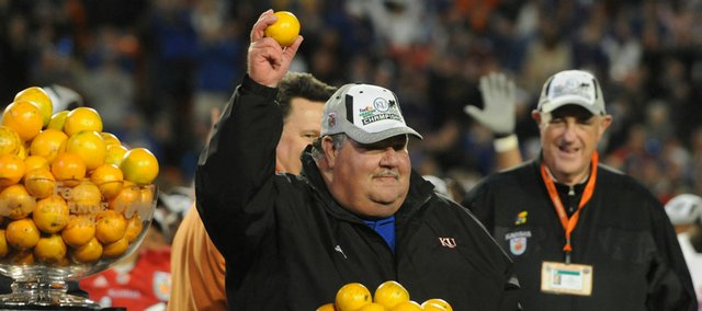 Kansas coach Mark Mangino holds aloft an orange as KU athletic director Lew Perkins, right, looks on.