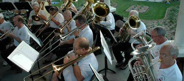 Members of the Lawrence City Band perform on the bandstand while children and their parents play in the South Park fountain in the distance in this 2006 file photo. The summer concert series begins again Wednesday.