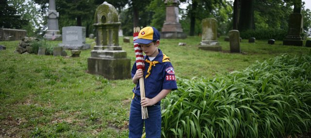 Cody Henderson, 7, pauses and reflects over a few gravestones Saturday while helping the Sons of Union Veterans of the Civil War mark Civil War veterans' graves with American flags at Oak Hill Cemetery. Just moments before, he was talking with his mother, Mary Henderson, about how young some of the people buried in the cemetery were.