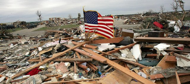 An American flag waves atop a home in ruins Tuesday in Parkersburg, Iowa. On Sunday, an extraordinarily powerful twister ripped apart Parkersburg, destroying 288 homes in the town of about 1,000 residents.