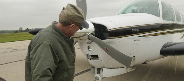 Dick Martin, 72, of Lawrence, surveys the damage to his Beechcraft airplane Wednesday after landing at Lawrence Municipal Airport without his landing gear. Martin, who before the incident hadn't damaged a plane since he began flying in 1962, forgot to drop the landing gear.