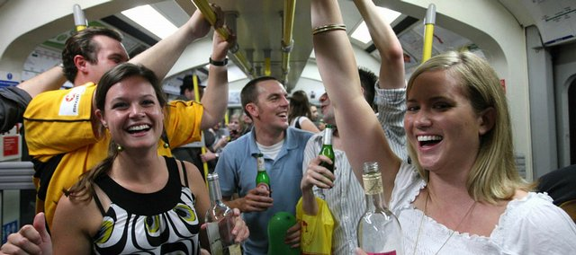 Revelers drink alcohol on a Circle Line subway train Saturday in London before the ban on drinking alcohol takes effect today.