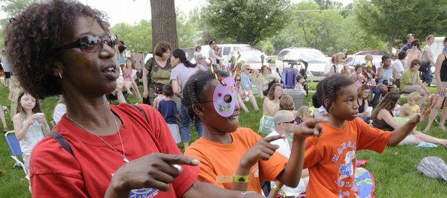 From left, Phyllis Wilson, Lawrence, and her daughters Raejaan Spicer, 11, and Raemona Spicer, 10, sing and dance along to a song by Dino O'Dell and the Veloci-Rappers on Saturday outside the Lawrence Public Library. The library kicked of its summer reading programs with various activities, including the band, a K.C. Zoo Zoomobile and crafts.