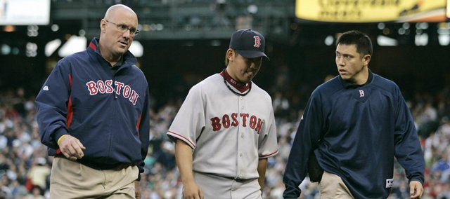 Boston pitcher Daisuke Matsuzaka, center, walks off the field with a trainer, left, and his interpreter Tuesday in Seattle. Matsuzaka suffered a shoulder injury and was placed on the DL after the game, but hopes to be activated by June 12.