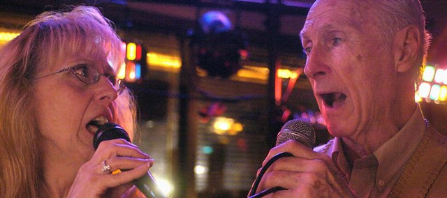 "Pat Smith, left, and Jerry Brown sing a duet last month at Legend's Sports Bar in St. Joseph, Mo. Brown, known by the nickname ""Downtown,"" is 80. Smith is his girlfriend, and the two are passionate about karaoke."