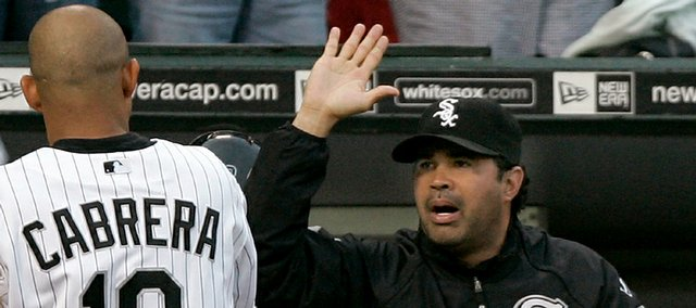 At right, White Sox manager Ozzie Guillen high-fives Orlando Cabrera after he scored. The Chisox defeated the Royals, 9-5, Tuesday in Chicago.