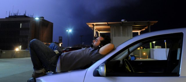 Lawrence resident Carl Masters kicks back with his iPod on the hood of his car at the city parking garage as a severe thunderstorm roles through town Thursday, June 5, 2008.
