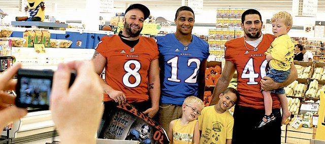 KU football players, from right, Mike Rivera, from right, James Holt and Joe Mortensen pose for a picture with cancer survivors Friday at Alex's Lemonade Stand at Hy-Vee, 4000 W. Sixth St. Alex's Lemonade Stand Foundation is an organization focused on raising money to fight children's cancer. The children, from right, are Lane Cunningham, 2, Isaac Greenly, 5, and Carson Toews, 4. On the left, Kristi Toews, Carson's mother, giggles at the children as Kara Cunningham takes a picture.