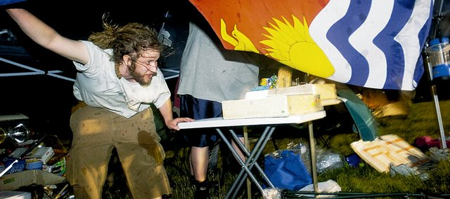 "Adam Gross, Topeka, holds down ""Paul and Chrissie's Free Stuff Tent"" on Thursday, June 5, 2008 during a thunderstorm at the Wakarusa Music and Camping Festival."