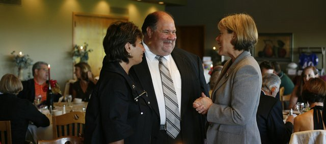 Kansas football coach Mark Mangino, center, and his wife, Mary Jane, left, chat with Congresswoman Nancy Boyda during a Lawrence Community Shelter fundraiser. Mangino co-hosted the event with artist Stan Herd on Friday at Alvamar Country Club. Donations from Mangino and Herd were auctioned off to help the Lawrence Community Shelter.