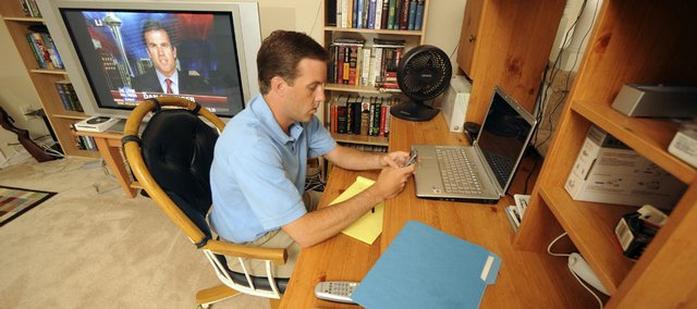 Brent Cranfield works from his home on May 29 in Marietta, Ga. He telecommutes one day a week, saving 30 or 40 miles on his car weekly. His office uses video conferencing, instant messaging and other communications technology to stay connected.