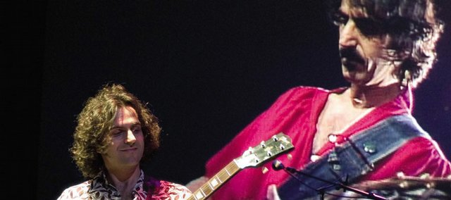 Dweezil Zappa, left, is flanked by a video of his late father, Frank Zappa, during a Zappa Plays Zappa concert.