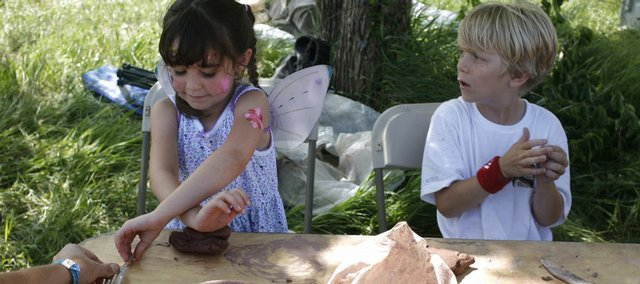 Riley Fullerton, 5, of Baldwin City, left, and Rowan Laufer, 7, of Lawrence, work with clay Saturday at the Lawrence Arts Center's tent at the Wakarusa Music and Camping Festival at Clinton State Park. The four-day festival, often associated with more adult activities, has many family-friendly options.