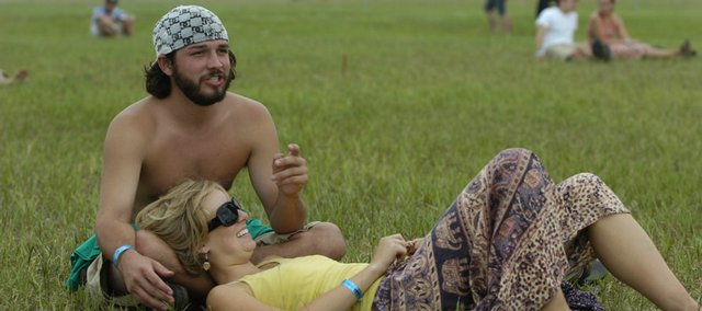 Lane Westbrook, of Austin, Texas, and Sandy Pedersen, of Boulder, Colo., rest on some open grass and wait for another show to begin Sunday at the Wakarusa Music and Camping Festival.