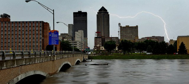 As rising floodwaters of the Des Moines River approach a closed downtown bridge, a thunderstorm crosses Des Moines, Iowa, dropping more rain on Wednesday. The rising river will cause severe flooding in downtown Des Moines and other parts of the capital metro area. More rain is expected through today. Flooding is also ravaging other parts of eastern Iowa, while tornadoes raked the western part of the state on Wednesday night.