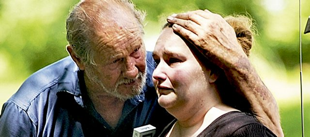 Gary Roit, left, consoles Shannan McCawley on Friday as they clean out the charred remains of McCawley's house at 1141 N.Y. A fund has been established at Douglas County Bank to help the family.