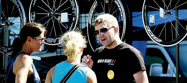 From left, Karen Buxton, of Greensboro, N.C., and Leslie Curley, of Topeka, talk with Patrick Geren, of Omaha, Neb., about energy supplements during the Ironman 70.3 Kansas expo at the corner of Ninth and New Hampshire streets. The triathlon starts Sunday morning at Clinton Lake.