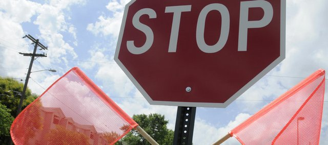 Drivers pass by orange flags attached to two new stop signs near the intersection of 11th and Mississippi streets in this file photo from June. According to city records, stolen signs add up to $30,000 in taxpayer losses each year.