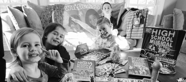 "Three-year-old Talya Appelbaum, left, sits for a photo with her sisters, Julia, 7, Lilly, 4, and brother, Joshua, 9, amongst memorabilia from the movie ""High School Musical"" at their home in Harrison, N.Y. Some parents are worried about values toddlers might be learning from the popular Disney franchise."