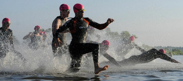 Athletes take to the water during the swimming competition at the Ironman 70.3 Kansas, the first of the competition's three legs, Sunday morning at Clinton Lake. An estimated 4,000 spectators cheered on more than 1,000 athletes.