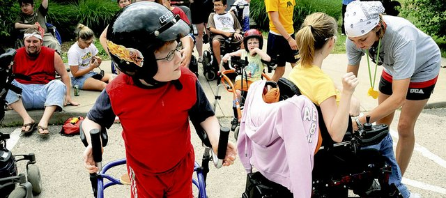 Luke Bruner, 9, Lawrence, center, waits his turn for a ride in a motorcycle sidecar last week at a Muscular Dystrophy Association summer camp at Tall Oaks Conference Center near Linwood. The weeklong camp, solely for kids with degenerative neuromuscular diseases, this year had 69 participants, each paired with a counselor for one-on-one attention throughout the week.