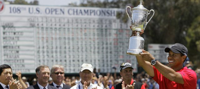 Tiger Woods is applauded while holding up the championship trophy. Woods held off Rocco Mediate, background on the right, to win the U.S. Open after a sudden-death hole following an 18-hole playoff on Monday in San Diego.