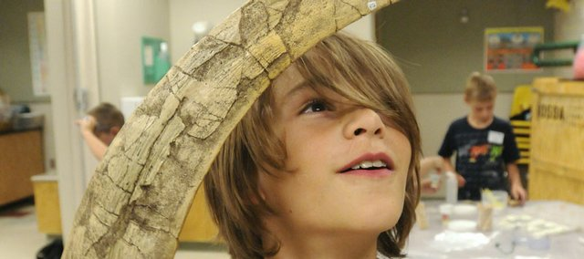 Caden Henry, 10, inspects a life-size reproduction of a claw from a Therizinosaurus, a 35- foot bipedal dinosaur with arms extending 8 feet. Caden was one of 11 youths who participated in the Dinosaur Detectives day camp Monday at Kansas University's Natural History Museum.