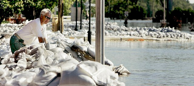 Bryan Schulte keeps watch over a sandbag levee holding back floodwaters from the Mississippi River on Tuesday in Burlington, Iowa. On the Illinois side of the river across from Burlington, a levee broke Tuesday morning south of Gulfport, Ill., forcing the closure of a bridge that connects the two cities.