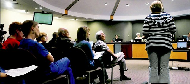 Audience members turn their attention to Lawrence resident Elizabeth Hatchett as she offers her opposition to a requested annexation of rural property along the Farmers Turnpike for industrial development. Hatchett spoke at Tuesday's City Commission meeting at City Hall.