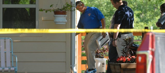 Investigators from the Douglas County Sheriff's Office put on plastic shoe coverings as they enter a home at 1602 N. 1500 Road, where a woman was injured on Thursday night.