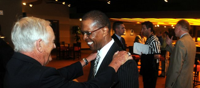 Famed Kansas University running back Gale Sayers, center, flashes a smile as he is greeted by longtime broadcaster Max Falkenstien in a lounge at the Sprint Center in Kansas City, Mo., in this file photo. Sayers has been hired by the KU athletics department to serve as Director of Fundraising for Special Projects.