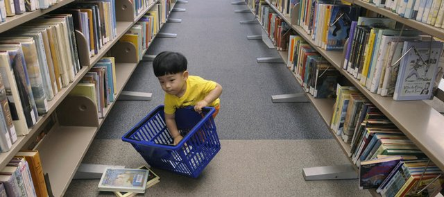 Jun Huh, 16 months old, picks up books from an aisle inside the Lawrence Public Library, 707 Vt.